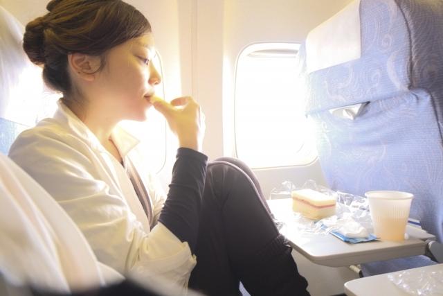 機内食を食べる女性